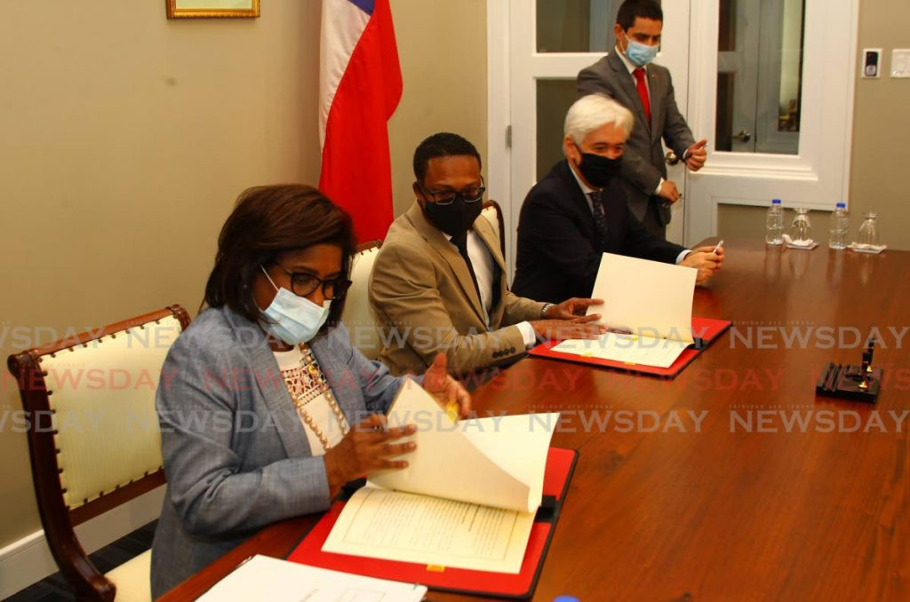 Hon Paula Gopee-Scoon, Minister of Trade and Industry (left), leads the signing of the General Framework Agreement, alongside her government colleague Hon Dr Amery Browne, Minister of Foreign and CARICOM Affairs and at right, H E Juan Anibal Barria Garcia, Ambassador Extraordinary and Plenipotentiary of the Republic of Chile to TT, assisted by Sebastian Anich, Deputy Head of Mission and Consul of the Embassy of Chile to TT, at the signing of the general framework agreement for the partial scope agreement between the government of the Republic of Trinidad and Tobago and the government of the Republic of Chile, Minister's Conference Room, Ministry of Foreign and CARICOM Affairs, Corner of Saddle Road and Prada Street, Queen's Park Savannah West, Port of Spain. - ROGER JACOB