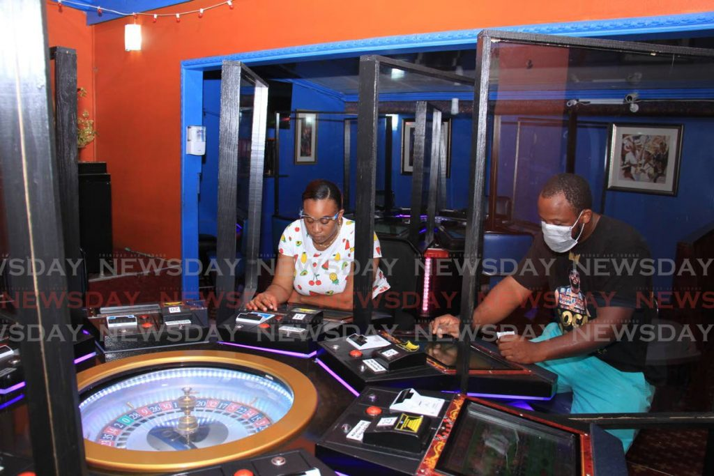 Nickesha Nottingham, marketing manager of the Jade Monkey casino, Crown Point, Tobago, and machine technician Marlon Edwards sit behind a roulette machine. The machines at the casino are now separated by plexiglass to help prevent the spread of the coronavirus.  - Ayanna Kinsale