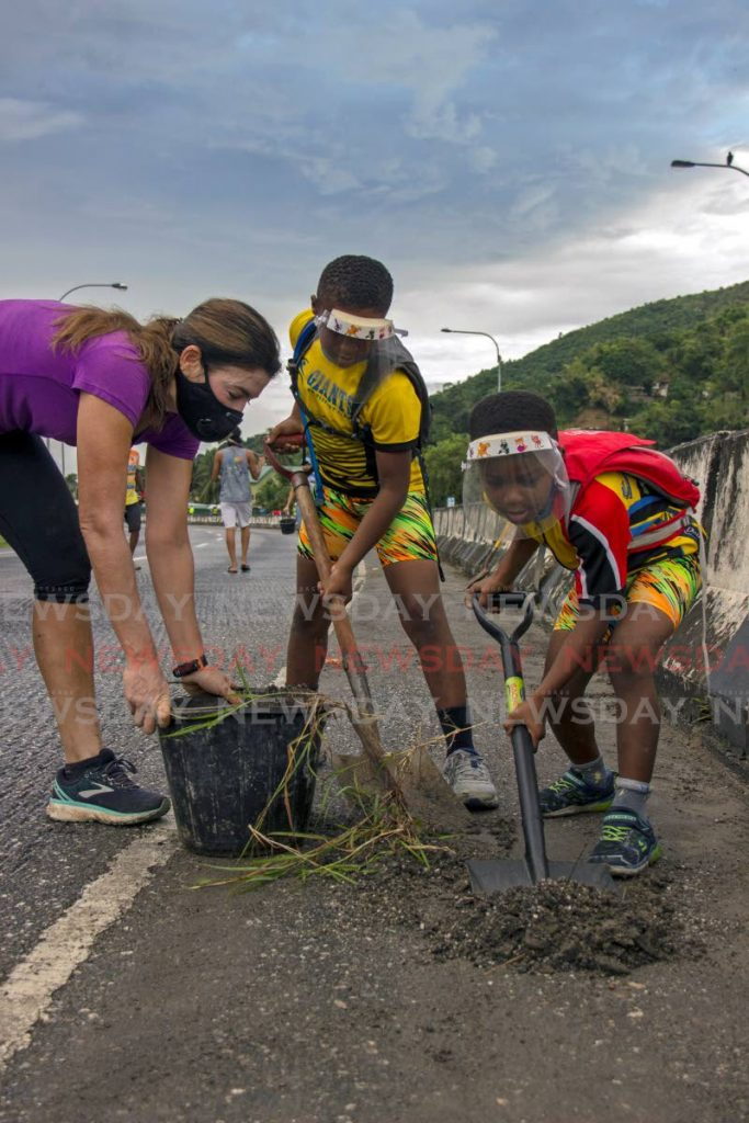 Nathaniel (centre) and Zachai Greaves, nine and six respectively, help Kerry Montano shovel dirt, grass and debris into a bucket as they help to clean a section of the Diego Martin Highway on October 25. A section of the Diego Martin Highway was recently milled to help prevent cars skidding off the road, but which has now made it almost unsuitable for road cyclists. The boys are members of Giants multi-sport club. - Melanie Waithe