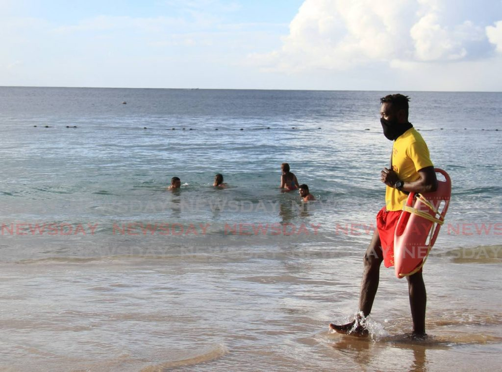 Lifeguard Kester Kent makes his rounds at Store Bay, Tuesday to ensure sea bathers are safe. PHOTO BY AYANNA KINSALE  -