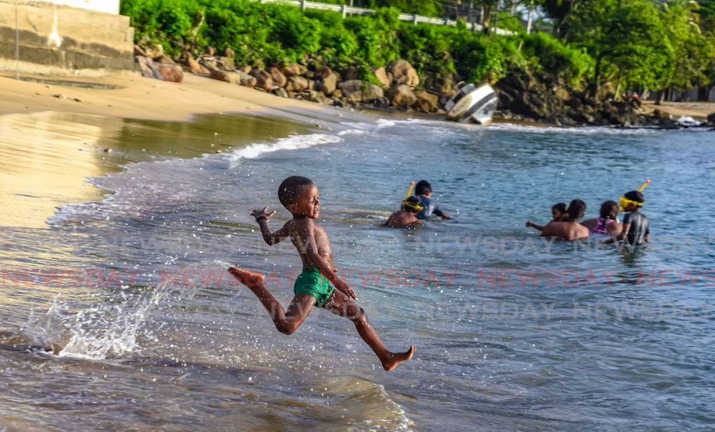 Three year old Kyle Moore makes his way into the water at Mt Irvine Bay, Tobago. - AYANNA KINSALE