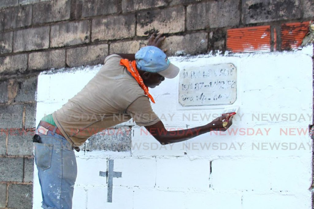 SPRUCE UP: Leon Phillip paints a  headstone at the Woodbrook cemetery on Friday in preparation for All Souls Day on Sunday.  PHOTO BY ROGER JACOB - ROGER JACOB