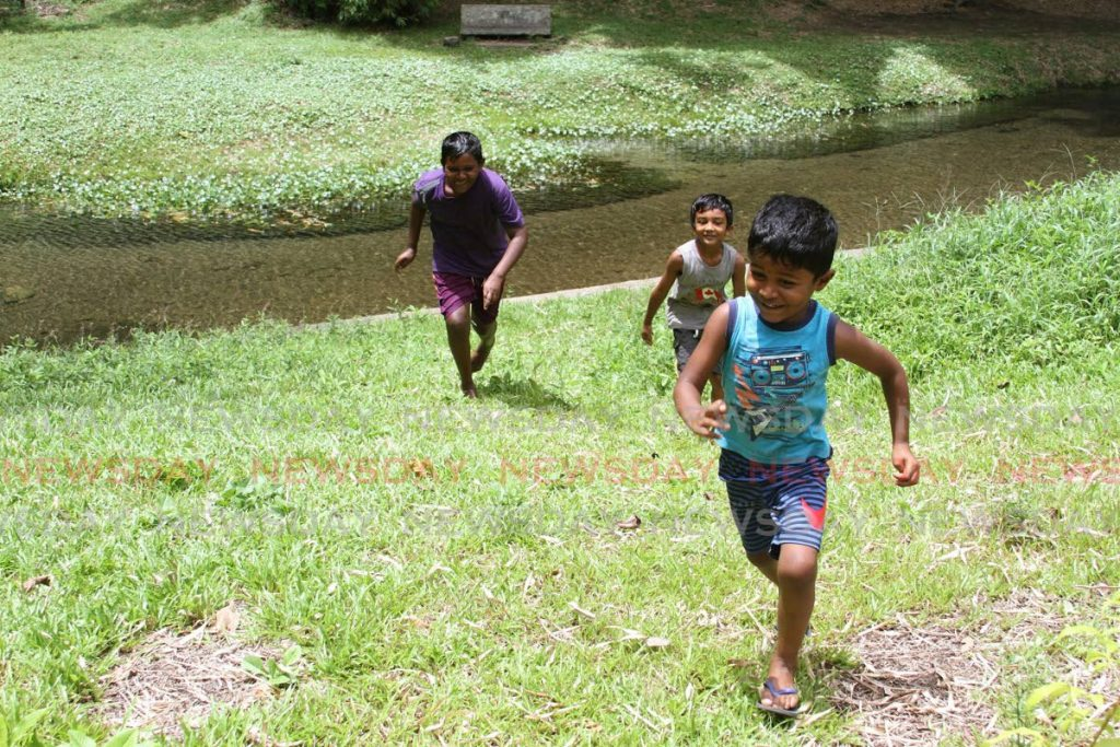 Children run up a hill at Caura River. - Angelo M. Marcelle