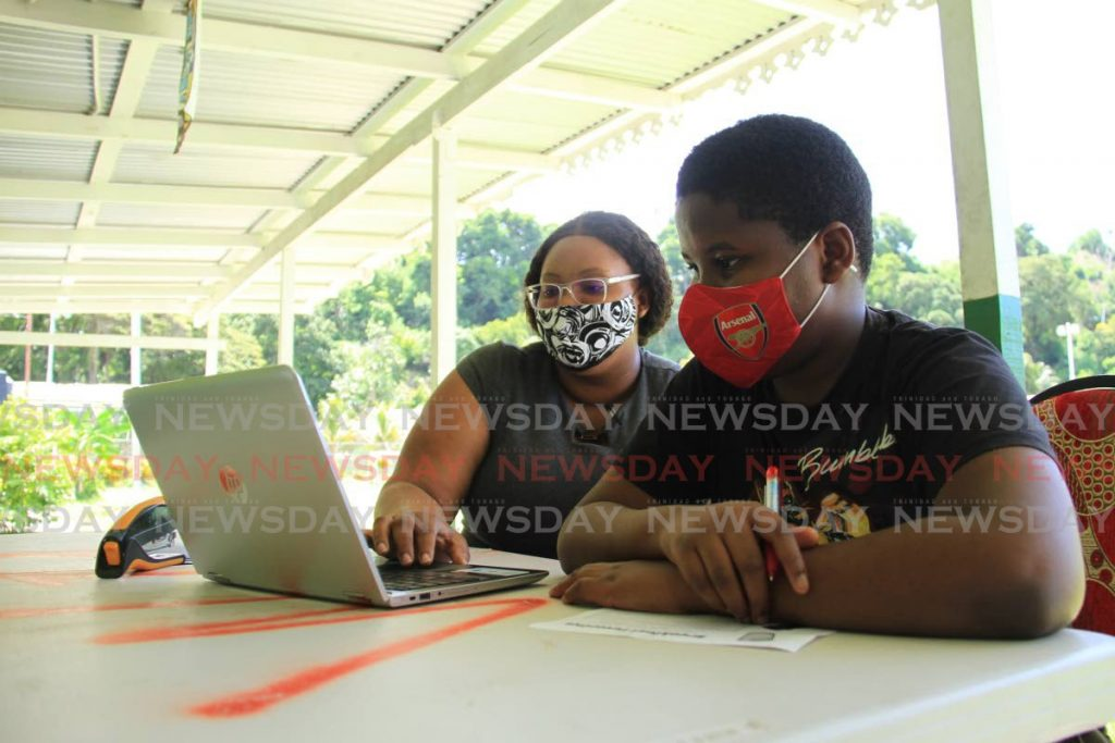 Lynelle Jordan gives Malique Toppin computer literacy lessons at the Roxborough Police Youth Club in September. In two years over 90 per cent of the island should have free WiFi. PHOTO BY AYANNA KINSALE  -