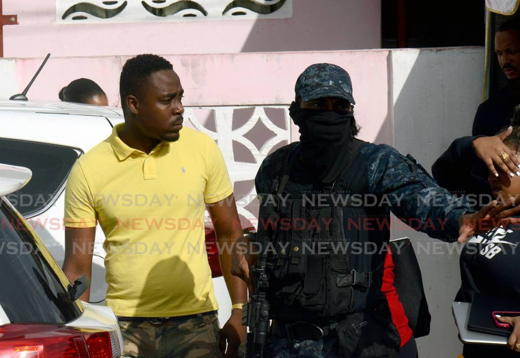 Drugs  Sou Sou founder Kerron Clarke, left, speaks to a masked police officer during a raid at his La Horquetta home on October 27. - ROGER JACOB