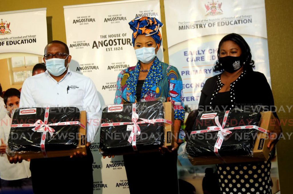 Angostura Holdings Ltd CEO Ian Forbes, Education Minister Dr Nyan Gadsby-Dolly and Winzy Adams -- vice principal of Bishops Anstey High School. one of the 18 schools to receive laptops, at the Ministry of Education in Port of Spain. - SUREASH CHOLAI