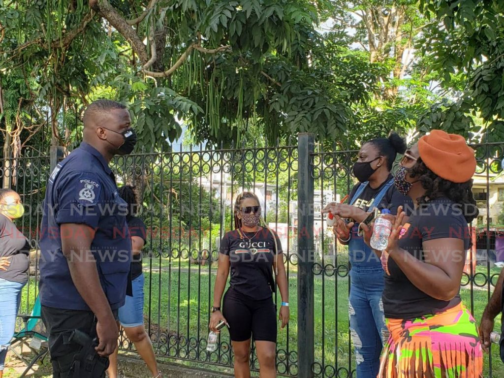 A police officer warns supporters of Drugs Sou Sou they could be charged for protesting outside the Prime Minister's residence in St Ann's on Saturday. - Janelle De Souza