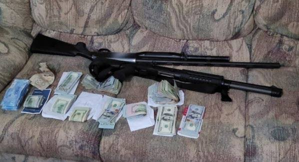 SEIZED: Cash and guns seized at a man's Preysal home on Monday. PHOTO COURTESY TTPS - TTPS