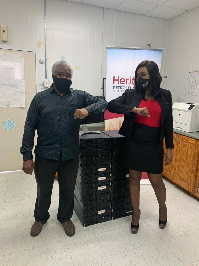 Heritage Petroleum Ltd corporate communications manager Arlene Gorin-George with the grandparent of a student who received a computer. Photo provided by Heritage. -