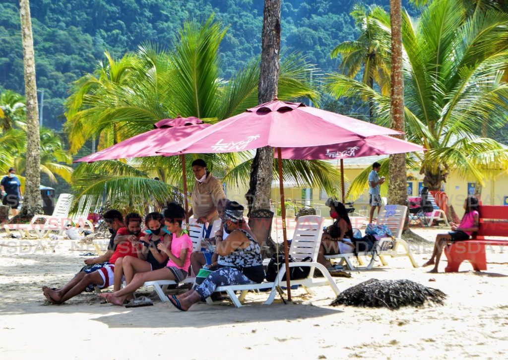 DEGREES OF COMPLIANCE: Some people relax on Maracas Beach on Sunday morning after Police Commissioner Gary Griffith and a team of officers visited to ensure covid19 regulations, especially as it relates to the wearing of masks, were being followed. - VIDYA THURAB