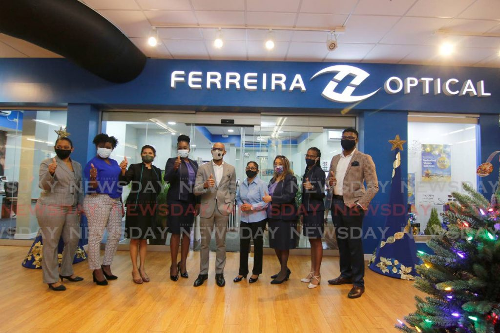 Ferreira Optical CEO Lorenzo Hodges, centre, with staff at the launch of the company's new branch inside Massy Stores' Gulf View branch in La Romain on Monday. - Marvin Hamilton