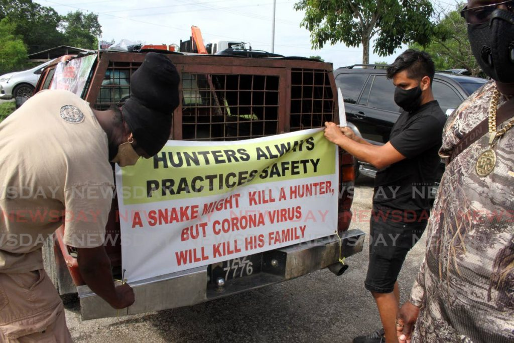 Hunters attach signs on empty hunting dog cages about how covid19 restrictions are affecting them during a protest at the Caroni Bird Sancutary, on Wednesday, for the hunting season to be opened. PHOTO BY ANGELO MARCELLE -