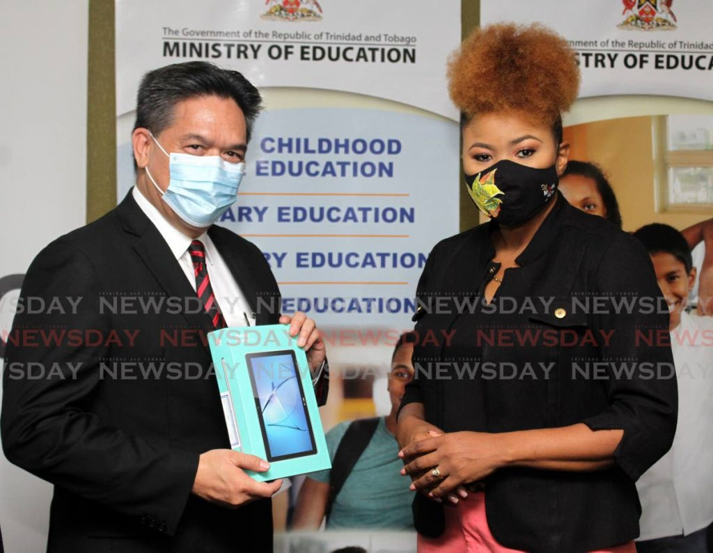 NGC president Mark Loquan presents Education Minister Dr Nyan Gadsby-Dolly with an electronic device at Education Towers, Port of Spain on Friday. The NGC group will donate $2 million in laptops and tables to the ministry's Adopt-a-School Initiative. PHOTO BY ANGELO MARCELLE -