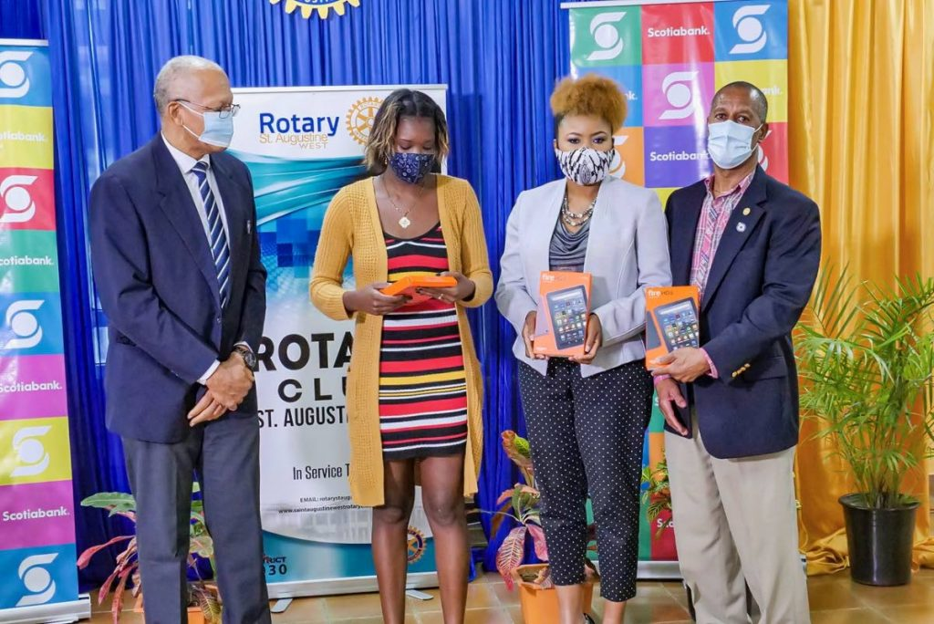 From left, past president of the Rotary Club of St Augustine West Stephan Gift, Tauriel Kelly, Education Minister Nyan Gadsby-Dolly and past president Adrian Saunders.  Kelly as given tablets for her children. The devices were donated by the Rotary Club of St Augustine West and the Scotia Bank Foundation on November 13. -