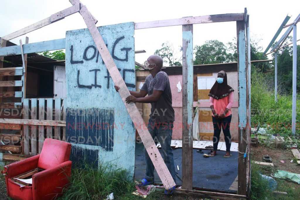 MASH UP: While his daughter Shirley, 13, watches, Christopher Wolfe demolishes their one-room house in Claxton Bay on Sunday after they received an eviction notice from the State. PHOTO BY CHEQUANA WHEELER  -