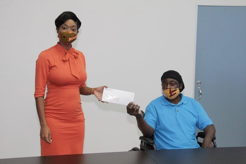 Assistant Secretary in the Division of Health, Wellness and Family Development Nadine Stewart-Phillips, left, presents a cheque to a man for medical aid.  - THA