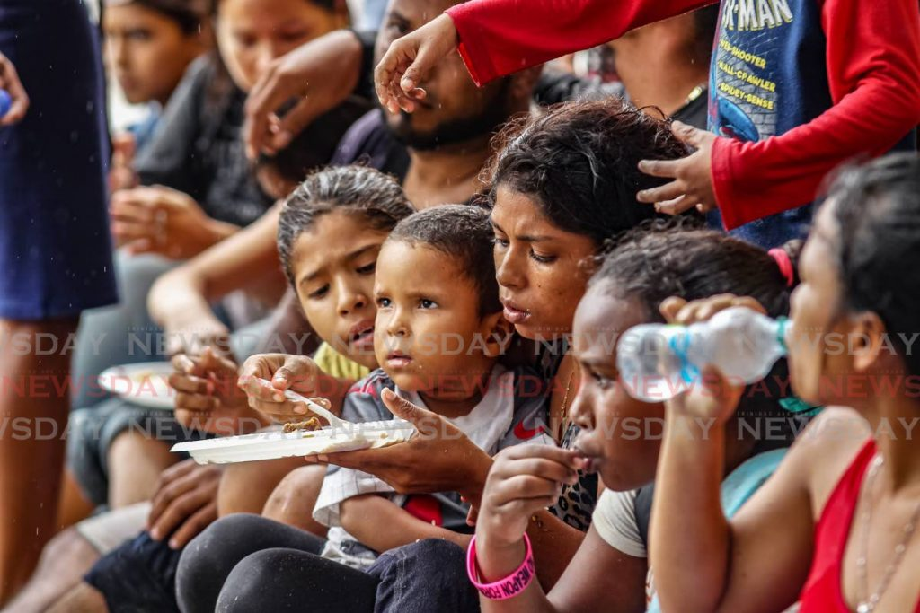 MEAL AT LAST: Children eat meals - their first since Sunday - shortly after arriving with their parents in a pirogue on Tuesday at Los Iros beach.  PHOTO BY LINCOLN HOLDER -
