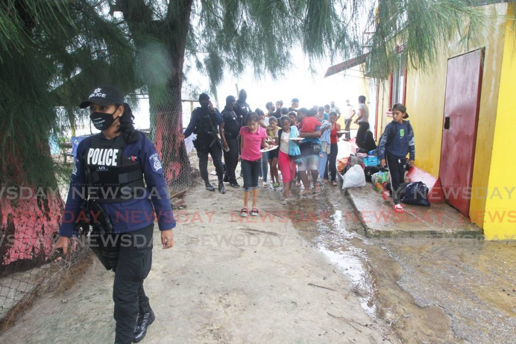 File photo: A policewoman escorts Venezuelans who arrived on pirogues at Los Iros, Erin in November. PHOTO BY LINCOLN HOLDER -