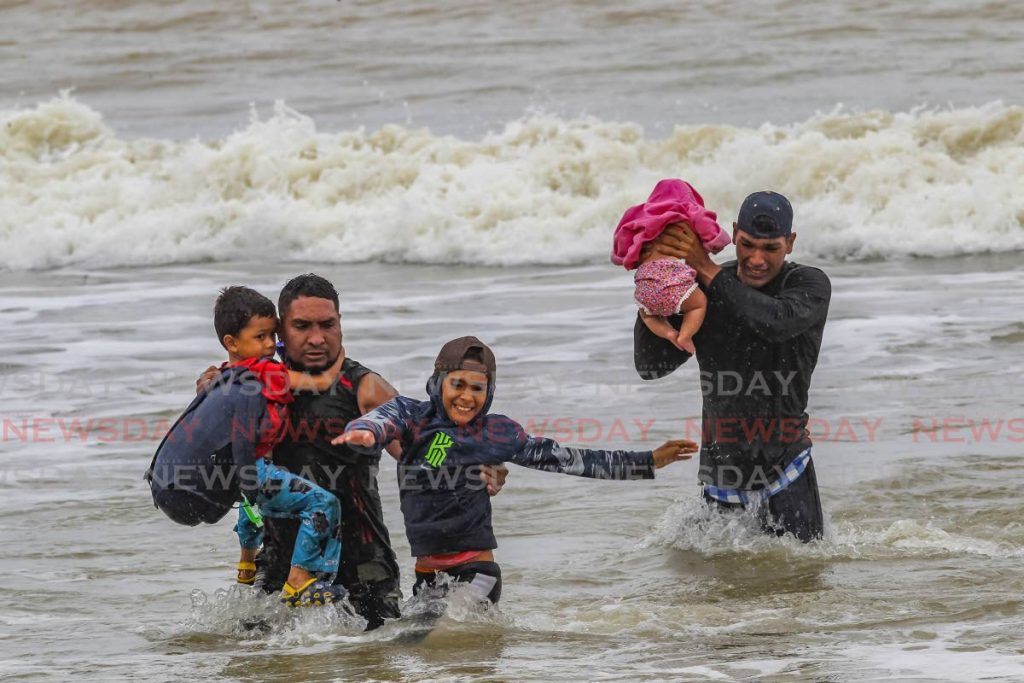 Venezuelan men and children make their way to shore after disembarking from a pirogue at Los Iros beach on Tuesday. They were among 16 children and nine adults who returned to Trinidad after being sent back to Venezuela in pirogues over the weekend. PHOTO BY LINCOLN HOLDER -