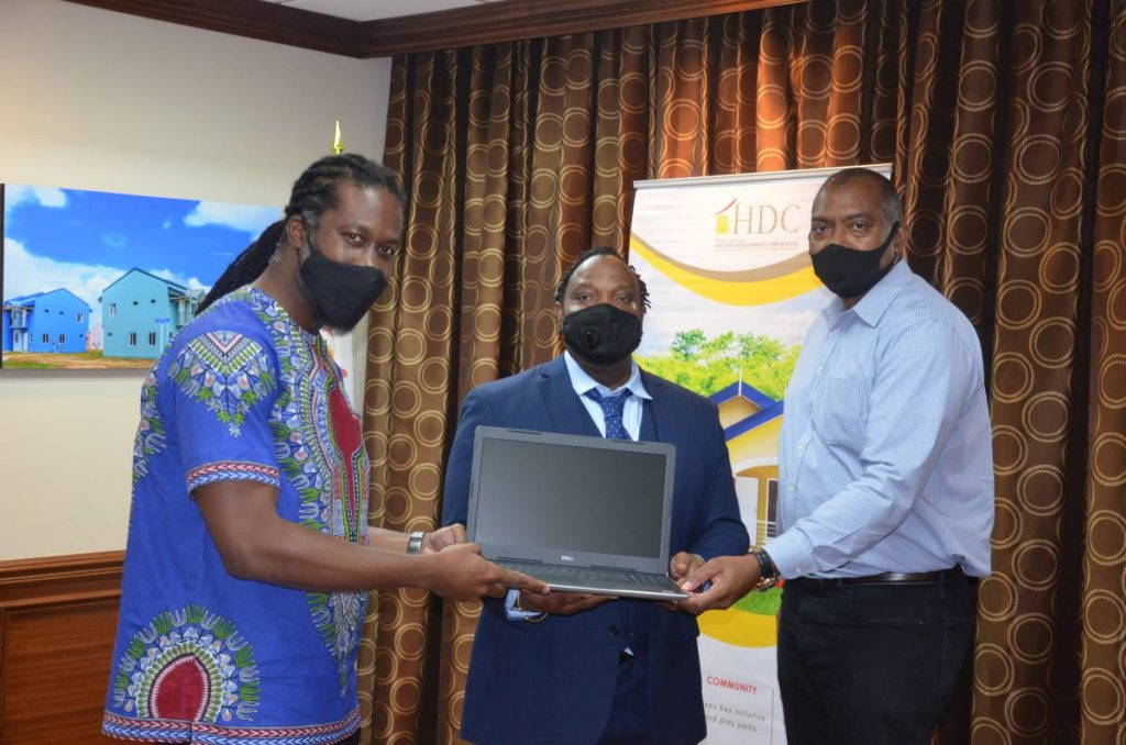 MP for Port of Spain South Keith Scotland (centre) receives one of the two laptop devices from Minister in the Ministry of Housing and Urban Development, Adrian Leonce (left) and HDC Managing Director, Brent Lyons (right). The laptops will be placed in the new study area/library which was created at the MP's office. - HDC