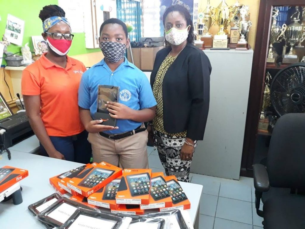 St Agnes Anglican School student Elijah Bentick, centre, recieves his new Amazon Fire tablet. He is flanked by his aunt Antonia Fortune, left, and principal Lauralyn Alexander-Olivier. -