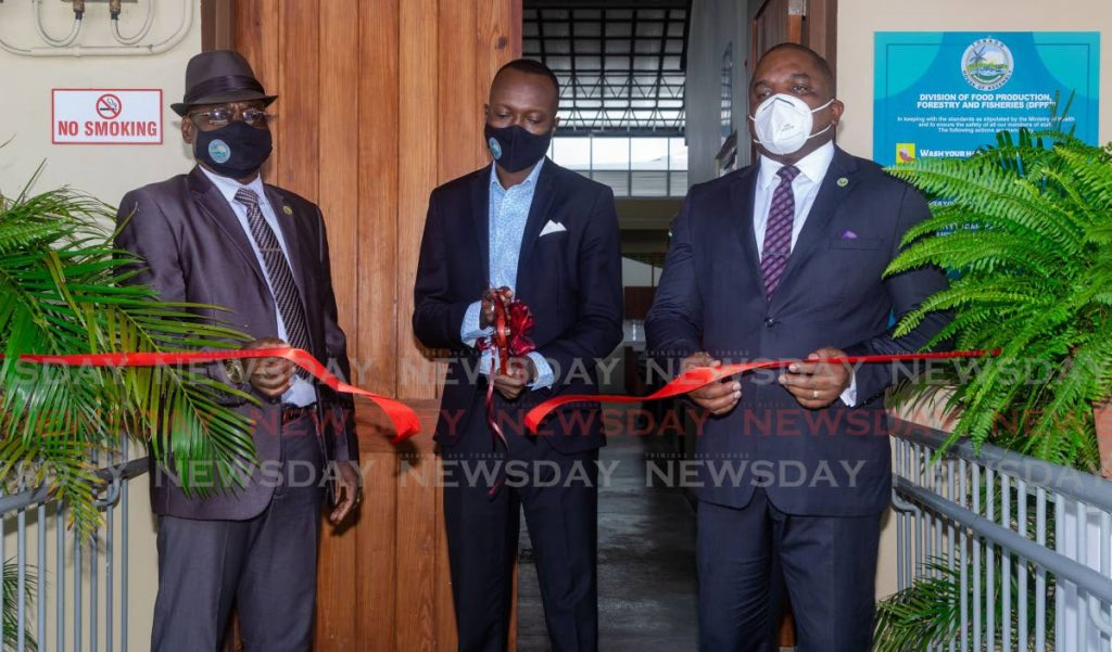 Chief Secretary Ancil Dennis, centre, cuts the ribbon to officially open the Scarborough market on Wilson Road on Monday. Also present at the ceremony were Secretary of Finance Joel Jack, right, and Secretary of Food Production Hayden Spencer. PHOTO BY DAVID REID -