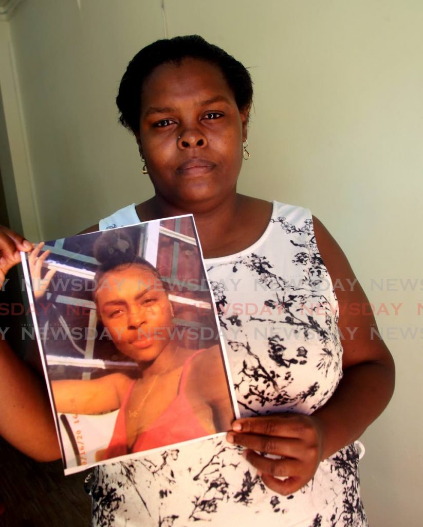 Candice Riley holds a photo of her daughter Ashanti Riley who went missing from her home in San Juan for several days before her body was found in Santa Cruz on Friday. PHOTO BY SUREASH CHOLAI  -
