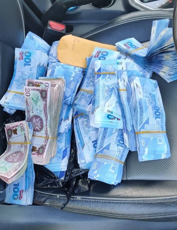 The wads of cash seized by police during traffic stop. - TTPS