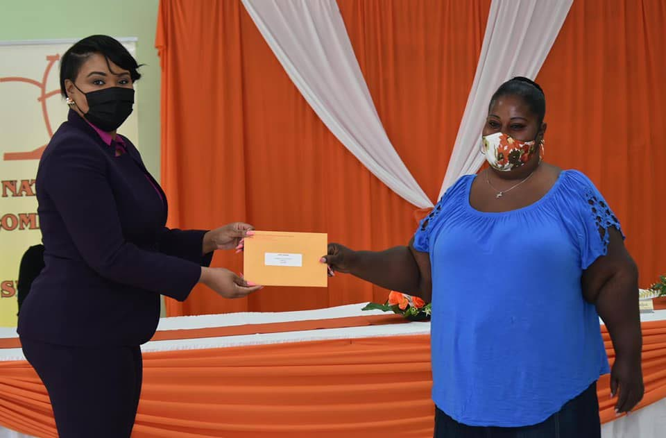 Tobago West MP Shamfa Cudjoe, left, hands out a cheque to one of the grant recipients at a distribution ceremony held by the National Self-Help Commission Ltd on Monday. -