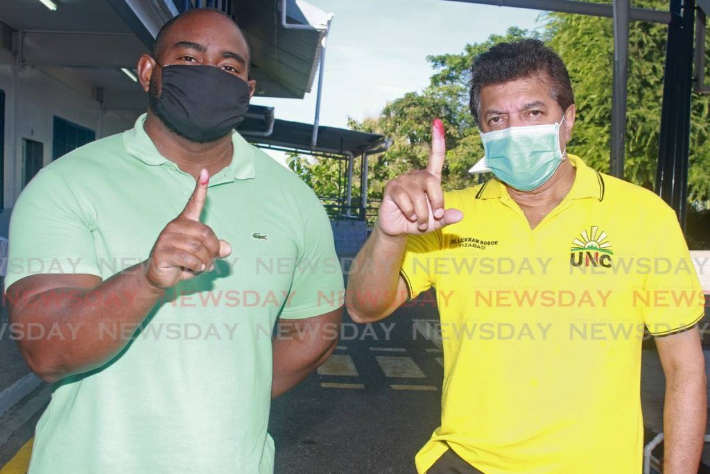 Former UNC Senator Sean Sobers and Fyzabad MP Dr Lackram Bodoe display their fingers after voting at Naparima College, San Fernando, in the United National Congress' internal elections on Sunday. - CHEQUANA WHEELER