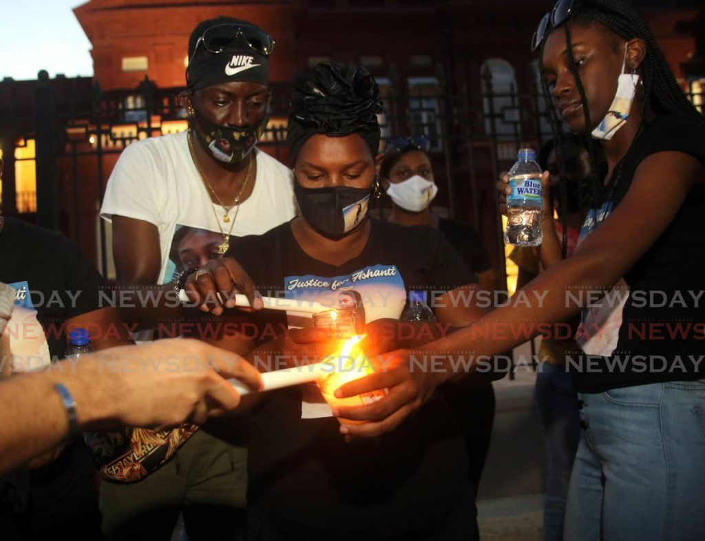 Candice Riley lights a candle with others in memory of her murdered daughter Ashanti during a vigil outside the Red House, after a motorcade from the family's home in San Juan to Port of Spain on Saturday. PHOTO BY SUREASH CHOLAI -