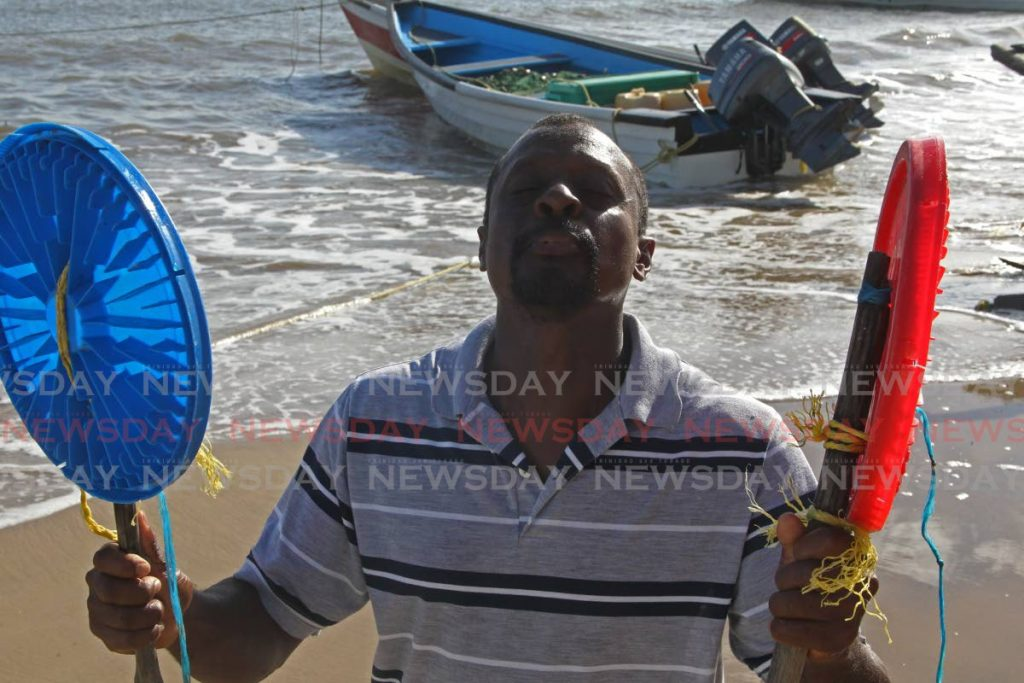 THANKFUL:  Guayaguayare fisherman Ryan Jones is thankful for the safe return of fishermen Shaquille Charles, Frank Anthony Sandy and Walter Whitemen after they were rescued on Tuesday. Jones is holding makeshift paddles the fishermen used while they were lost at sea for five days. - Marvin Hamilton
