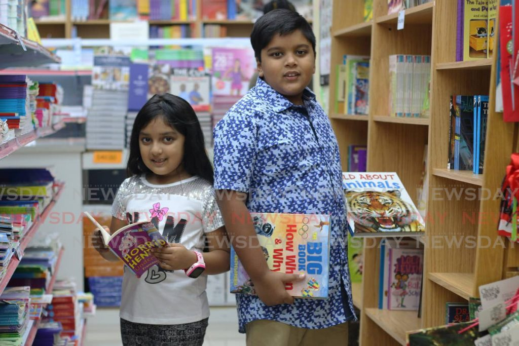 Josh Hansraj and his sister Sophia go through the books available at Nigel R Khan bookstore C3 Mall, San Fernando. Josh, eight, won the NGC Children's Bocas Lit Fest, Dragonzilla Short Story Writing Challenge for writers ages five to eight. -