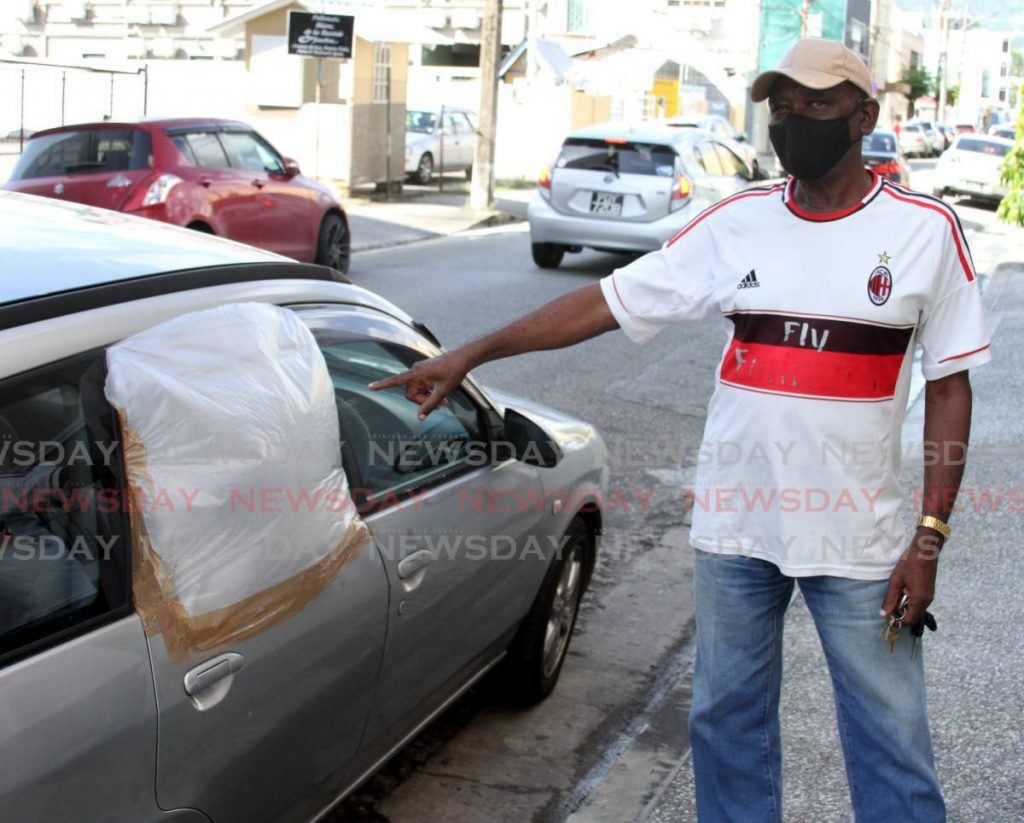 Foster Stewart points to his car window, now covered with plastic, after it was broken by a stone that flew from a weed wacker operated by HDC workers on October 22. - Angelo Marcelle