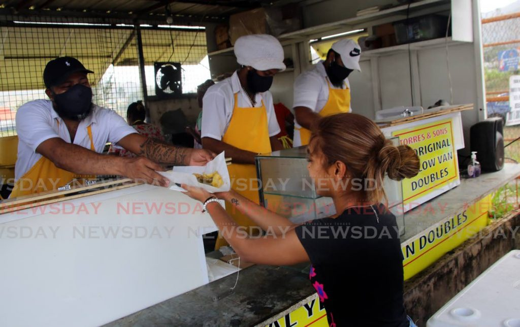 In this May 30, 2020 file photo a customer collects her doubles from the popular Yellow Van Doubles in Aranguez on International Doubles Day. FILE PHOTO/SUREASH CHOLAI -