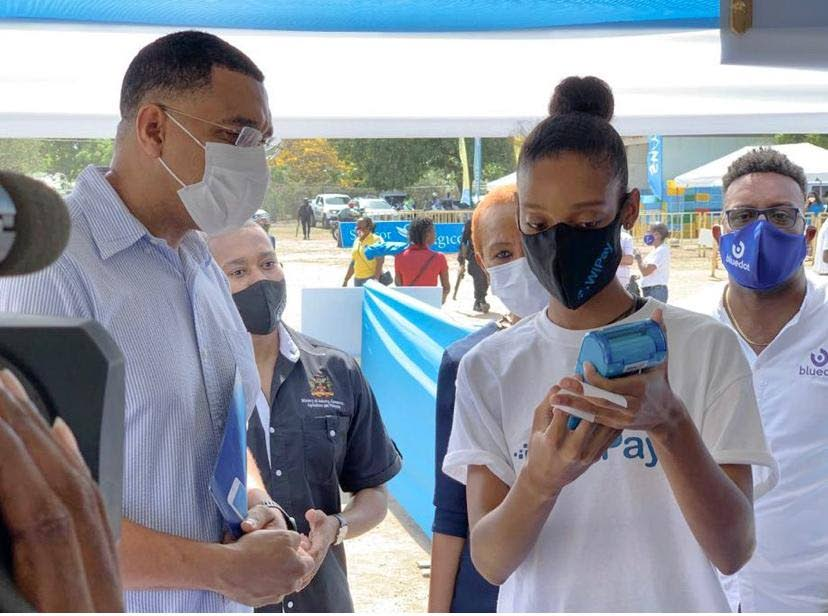 In this file photo, Jamaican Prime Minister Andrew Holness gets a demonstration from WiPay on its technology. Republic Bank has invested in a Wipay subsidiary. (Photo courtesy WiPay) -
