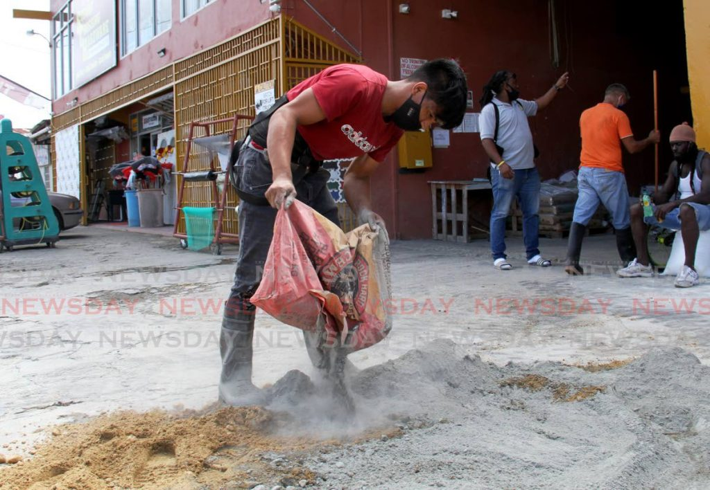 Jose Lopez throws out a bag of Rock Hard cement to mix at at Second Crossing Hardware, Bon Air Gardens, Arouca on January 2. - AYANNA KINSALE