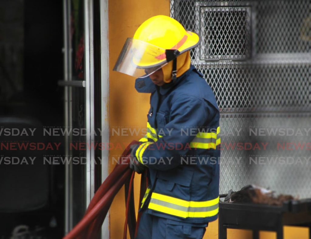 A firefighter moves a hose after putting out a blaze. File photo.  ROGER JACOB