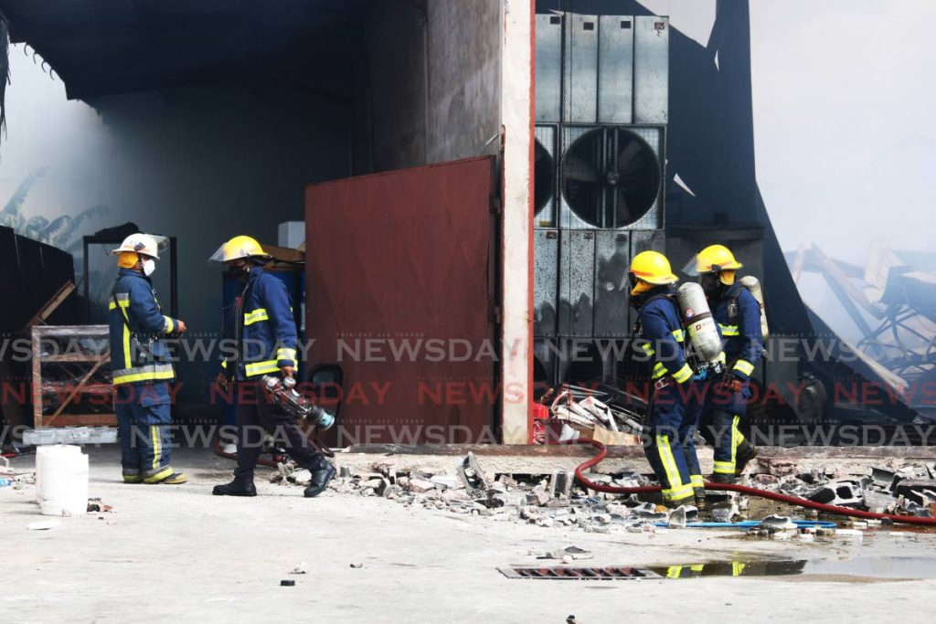 Fire officers a the destroyed warehouse at Enterprise, Chaguanas last Monday. - MARVIN HAMILTON