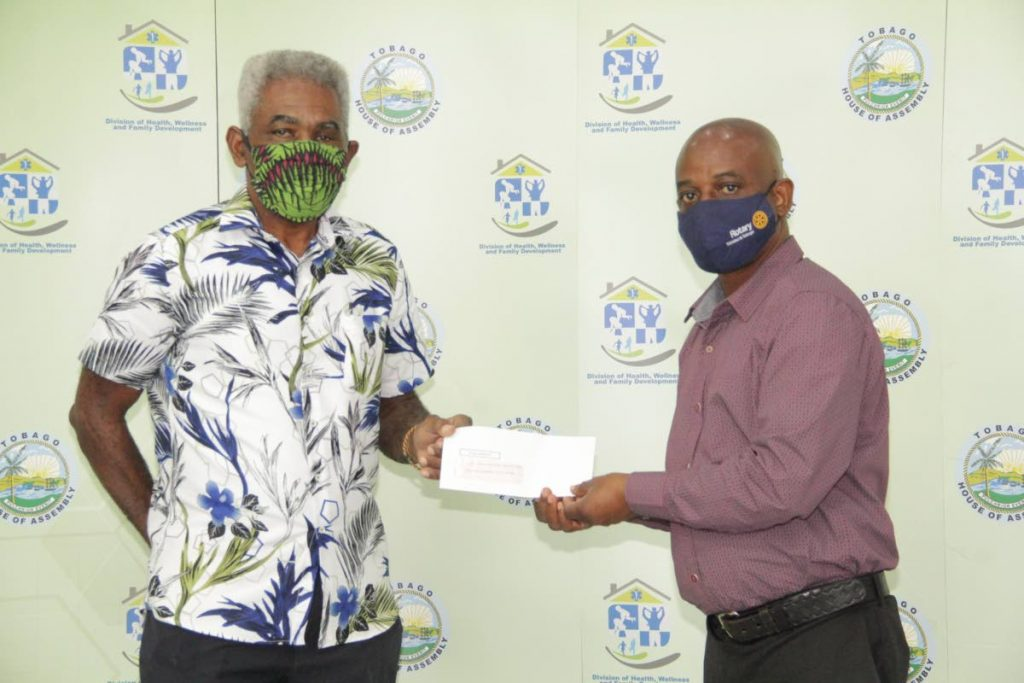 Dr Maxwell Adeyemi, right, chairman, medical assistance review committee, distributes a cheque to Randolph Roberts to cover medical expenses. - THA