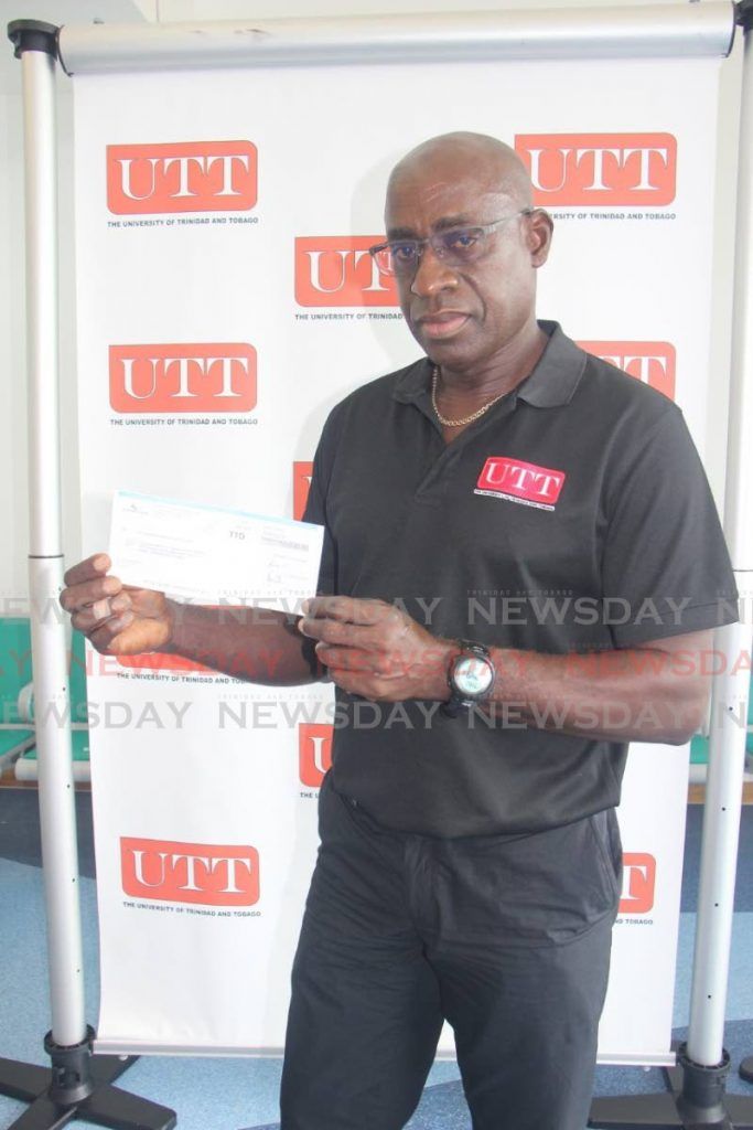 UTT men's football coach Clayton Morris with the cheque from Guardian Life of the Caribbean Ltd. -