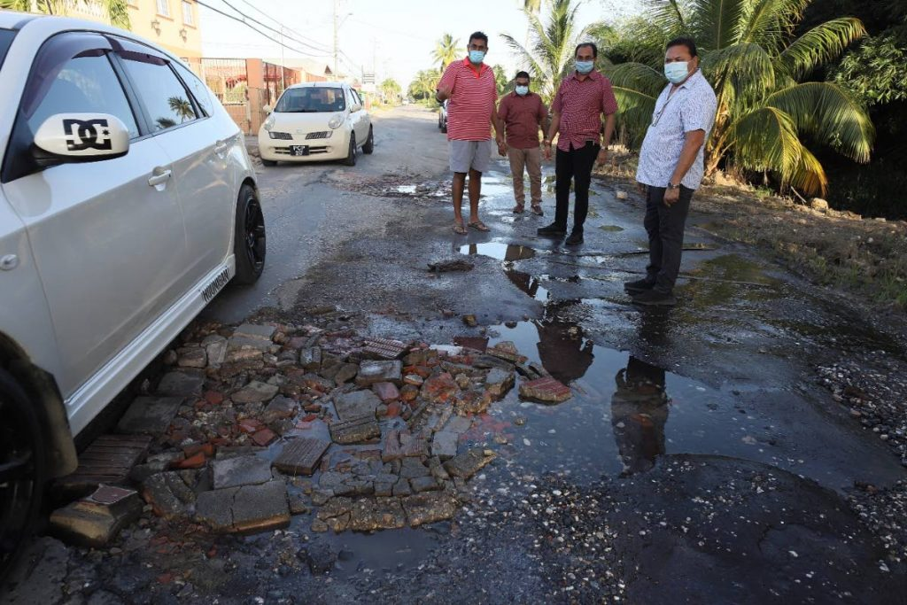 Chaguanas West MP Dinesh Rambally, third from left, listen to the complaints of Bejucal Road, Chaguanas residents about the poor condition of the road. -