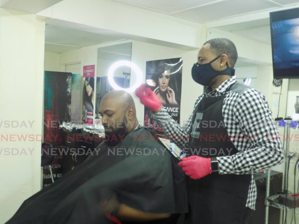 Mark Harrykissoon gets a quick trim from fellow barber Nigel Jerome at their Belmont Circular Road barbershop in December.  - Shane Superville