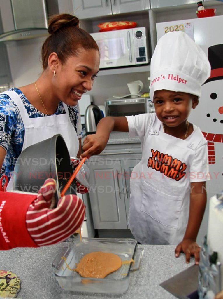 Zayn Pierre helps his mummy Elizabeth Cox make coconut fudge at their home in Chaguanas. PHOTOS BY ROGER JACOB  -