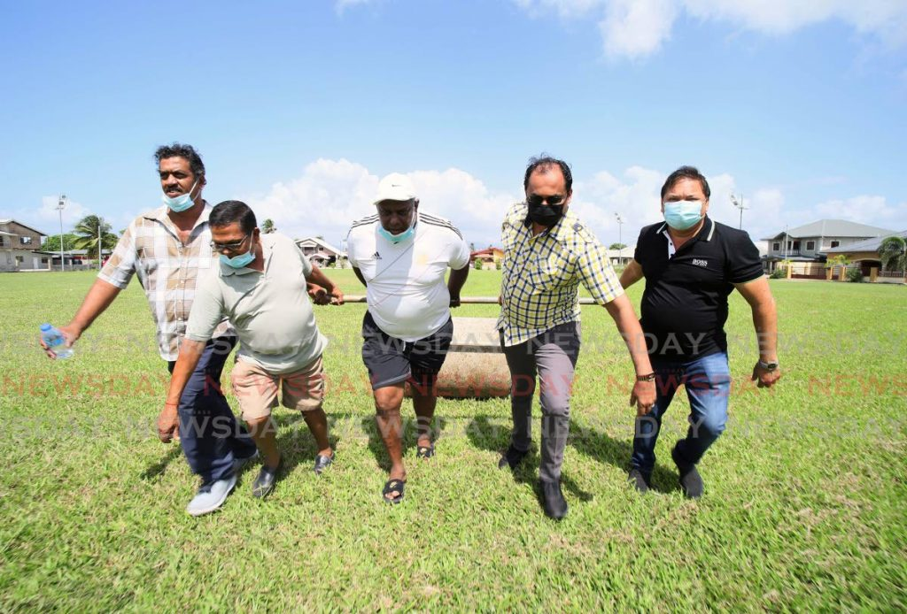 Central Sports president Richard Ramkissoon, right, and MP for Chaguanas West Dinesh Rambally, second from right, help groundsmen prepare the Central Sports ground in Chaguanas. Central Sports are hoping that the local cricket season will be allowed to resume soon.  PHOTO COURTESY TT CRICKET BOARD - TT CRICKET BOARD