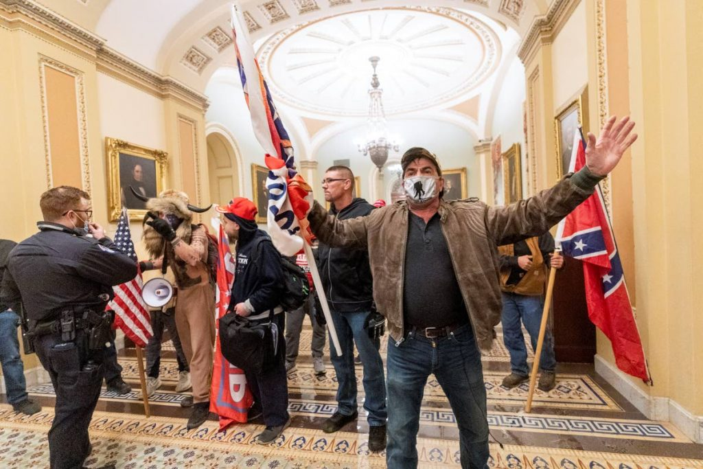 Supporters of President Donald Trump confront U.S. Capitol police officers outside the Senate Chamber inside the Capitol in Washington on January 6.  AP PHOTO -
