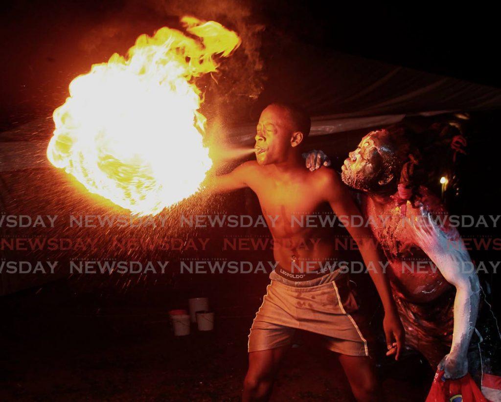Jab A Mien leader Keon Eccles, à droite, encourage Jamali Marchan 14, à cracher une boule de feu à la dernière ancienne caserne, Edna Hill Road, Arouca. PHOTO DE ROGER JACOB&#10 ; -