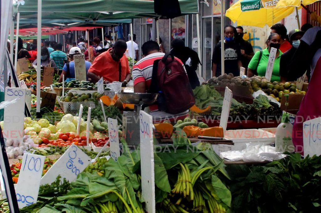 Customers buying their vegetables and fruits from vendors on the ever busy Charlotte Street in Port of Spain. - SUREASH CHOLAI