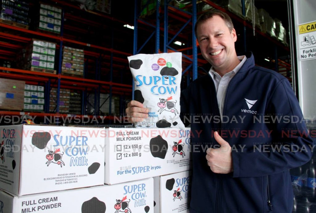 CEO of VEMCO Christopher Alcazar smiles with a pack of Super Cow milk.  - AYANNA KINSALE