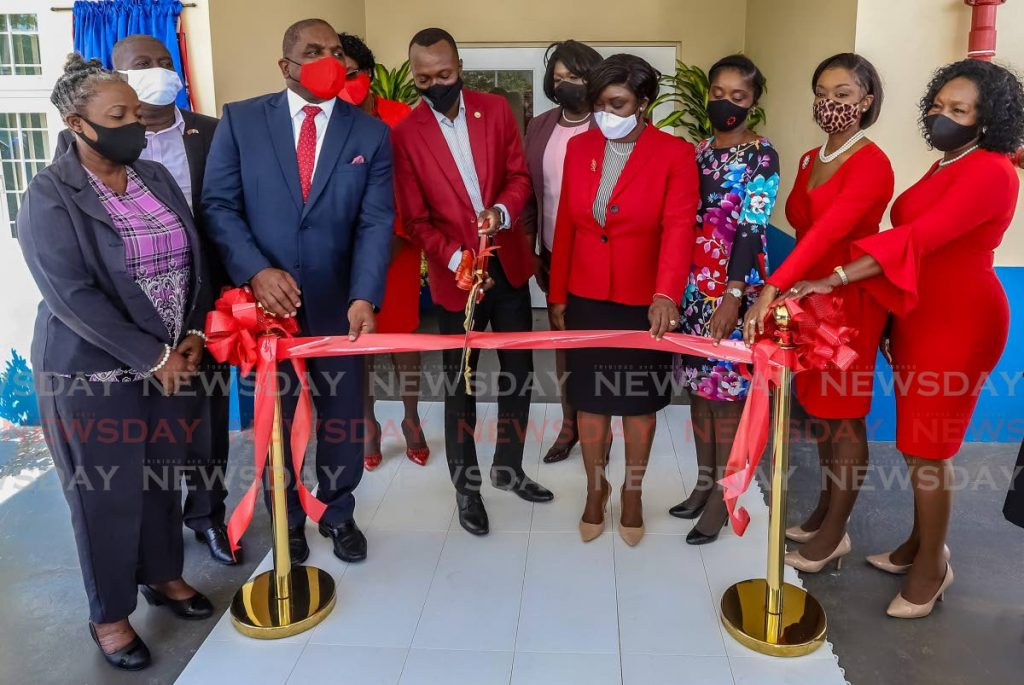 THA Chief Secretary Ancil Dennis cuts the ribbon to officially open the Moriah Health Centre, Moriah along with other officials on Friday. PHOTO BY JEFF K MAYERS -